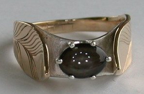 Gold Feathers and 8mm X 6mm Black Star Sapphire with Silver bridge